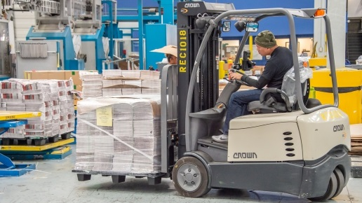 Forklift operator moving load through newspaper warehouse